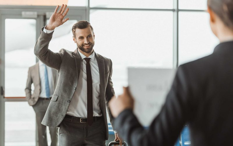 businessman waving to partner who waiting for him with name sign