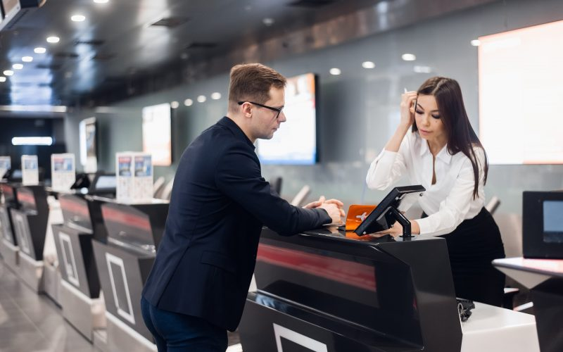 Staff At Airport Check In Desk Handing Ticket To Businessman