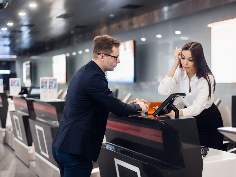 El personal del aeropuerto se registra en el mostrador entregando el billete al empresario.