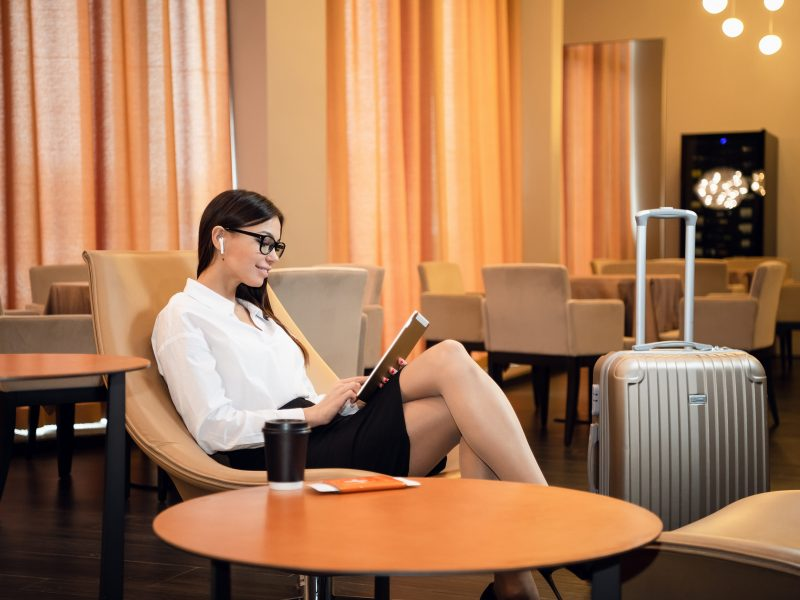 Confident businesswoman listening music on her tablet computer while sitting in chair in airport business lounge