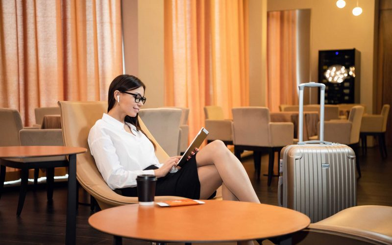Mujer de negocios segura de sí misma escuchando música en su tablet mientras está sentada en una silla en la sala de negocios del aeropuerto.