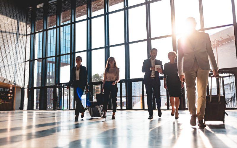 Un grupo de empresarios caminando por el vestíbulo del aeropuerto