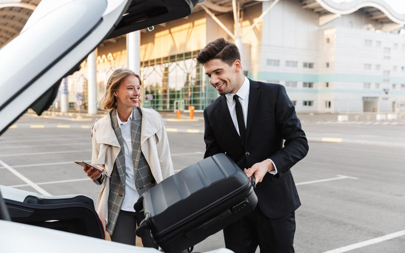 Image of young businesslike man and woman putting luggage in car