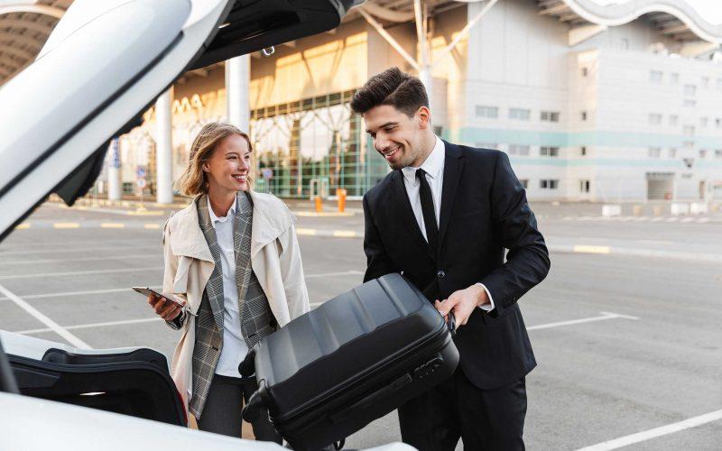 La imagen de un joven hombre y mujer de negocios poniendo el equipaje en el coche